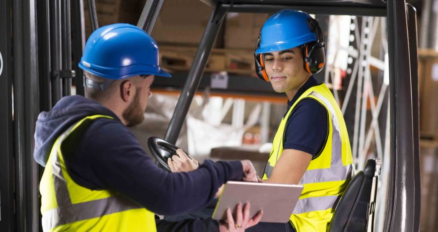 a mid adult male warehouse manager is chatting to  a young male colleague who is driving a forklift . Behind them can be seen a large warehouse interior .  the manager is explaining what he needs him to do and is showing him a digital tablet . The young man is listening . They are both wearing hi vis vests , and the forklift driver is wearing a hardhat and ear defenders .